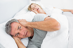 Husband covering his ears because of  his wife's snoring.
