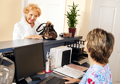 Mature female patient happily scheduling a recheck at the appointment desk of Sinus and Allergy Wellness Center.