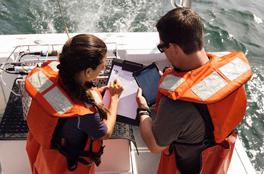 Photo of two people on a boat, wearing life jackets, discussing paperwork