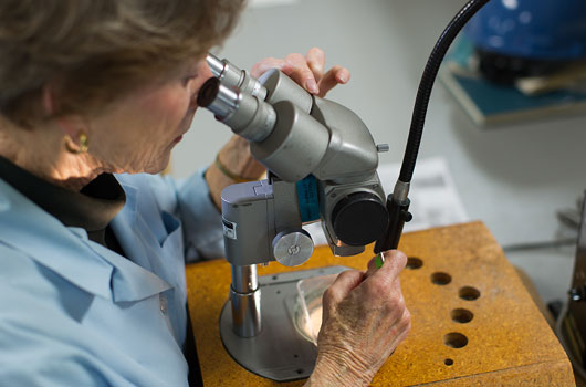 Photo of a woman looking through a microscope