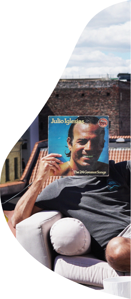 A man covering his face with a Julio Iglesias album