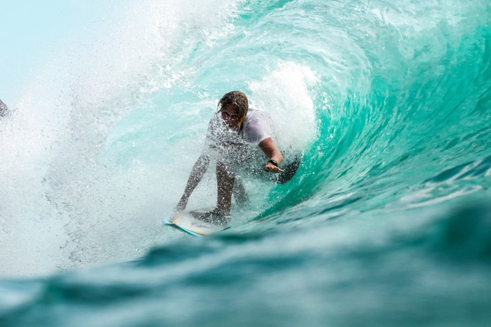 Man surfing getting barrelled in a pristine wave in Indonesia
