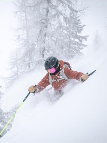 Skier sliding down powdered snow