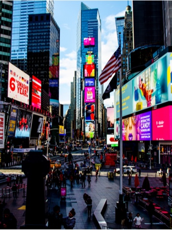 A busy street full of signs and screens in Times Square, New York
