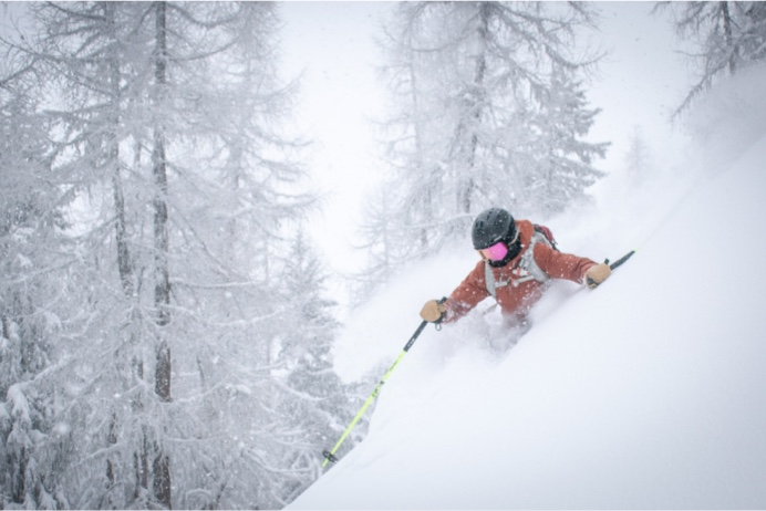 A man skiing down a powdery snowy slope