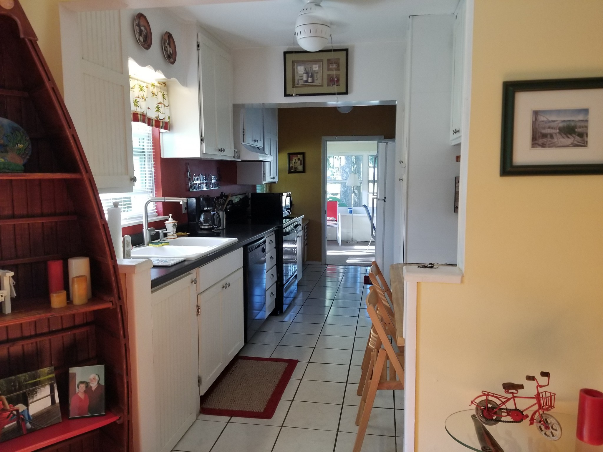 photo of kitchen with tiled floors, white cupboards, and a canoe-shaped shelf just outside the kitchen