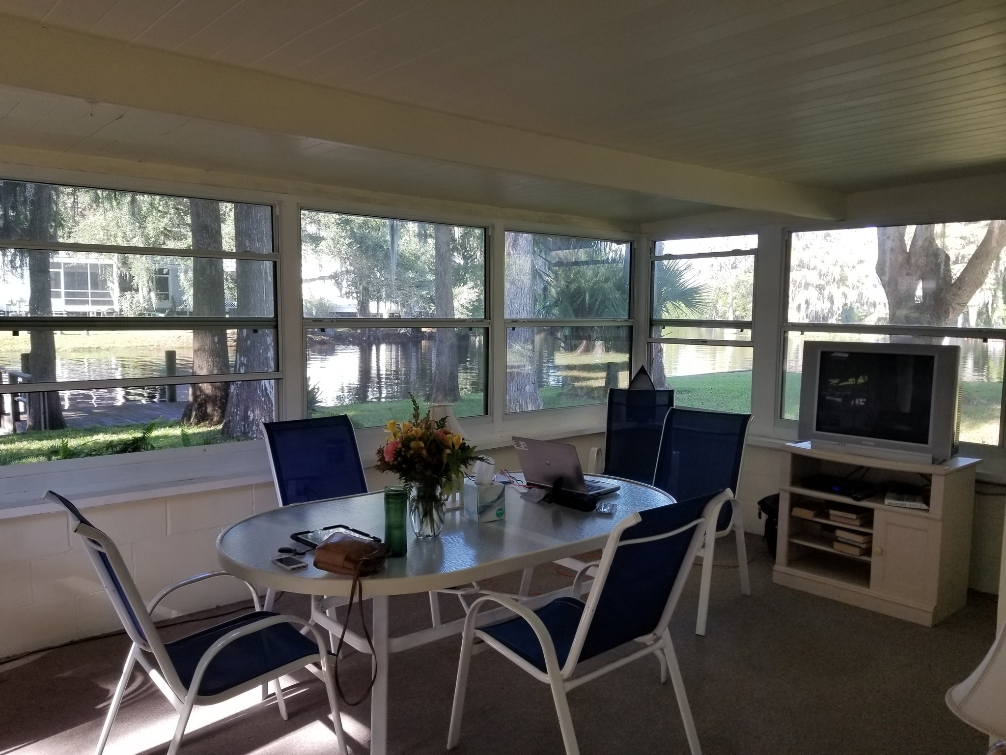 Photo of enclosed patio with 5 chairs. Small tv on shelves visible. Room with windows on all sides