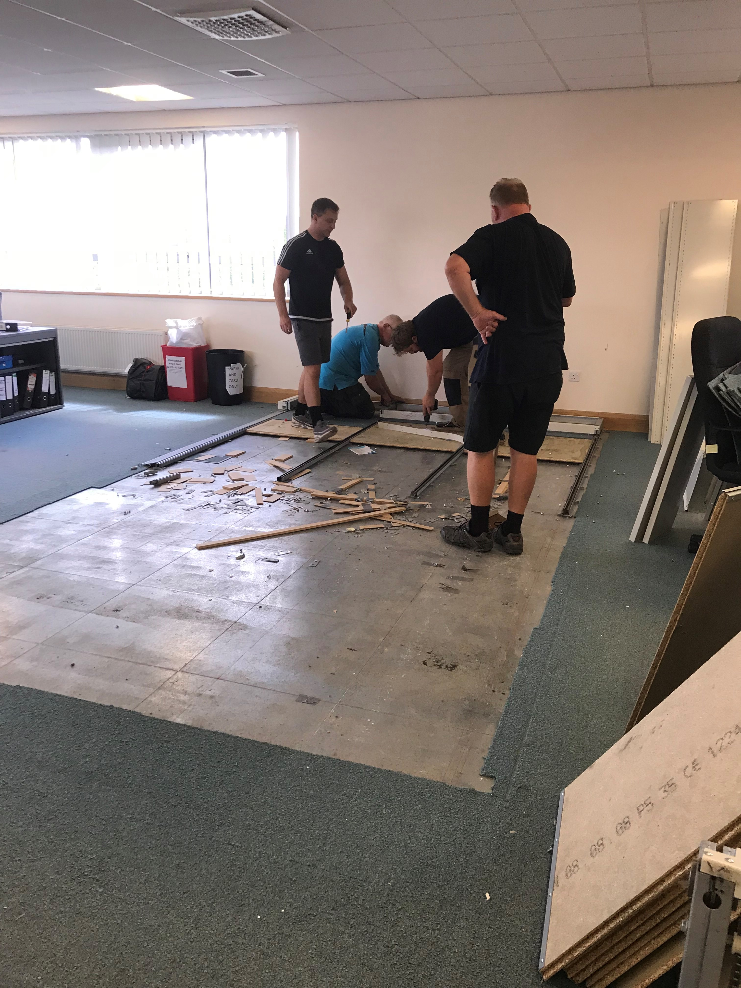 Office cleared of the large filing cabinets - workmen removing the remains