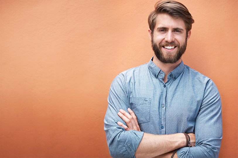 Male Real Estate Agent, smiling with crossed arms in a blue shirt