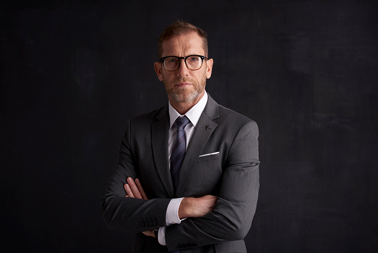 Middle ages, male banker wearing glasses. Wearing a dark grey suit and tie, standing in front of a dark grey backgroung
