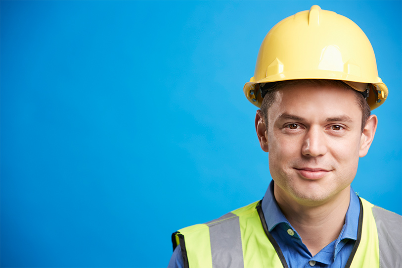 Young male construction worker, wearing a yellow hard hat, high-vis vest and blue shirt. Standing in front of a blue background