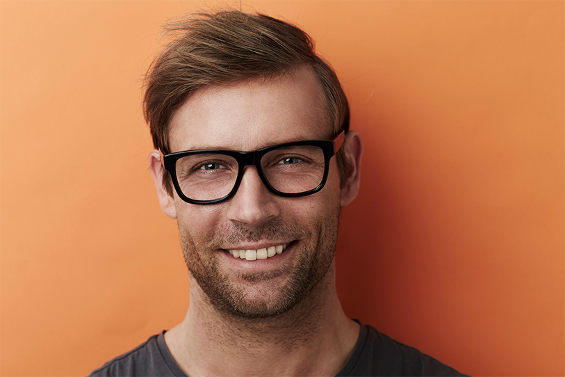 Young male engineer with brown hair and stubble wearing black rimmed glasses, standing in front of an orange background