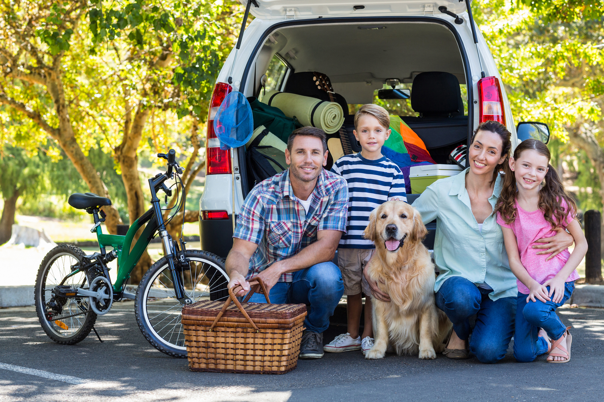 A family gets ready for a trip with their dog