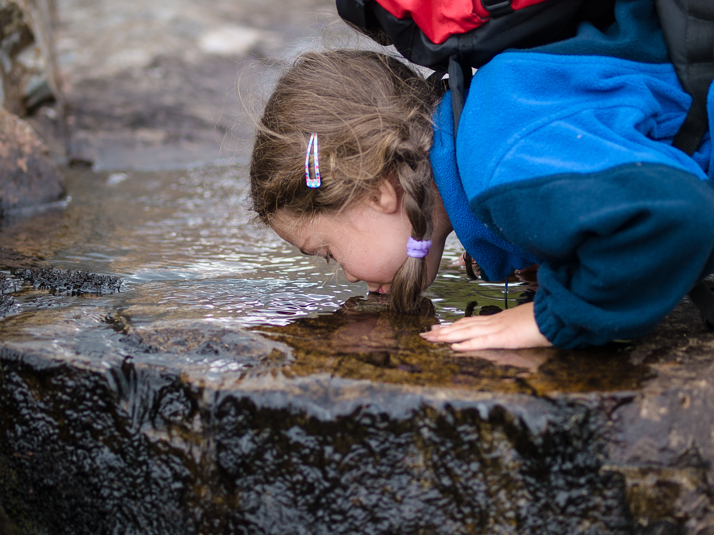 Girl drinking water of the streem