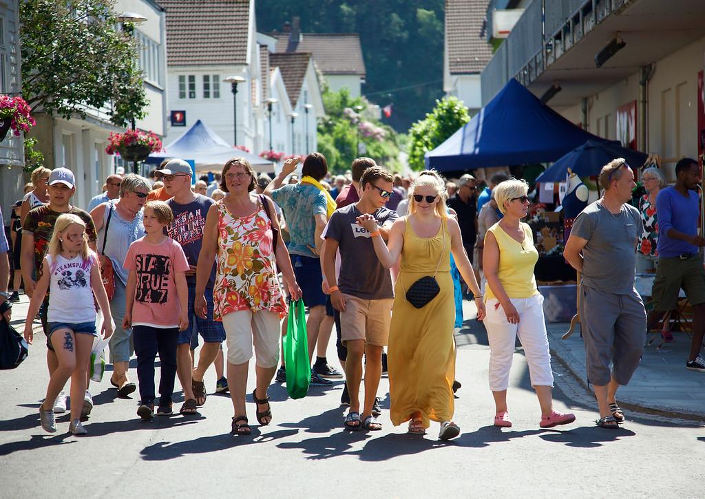 Mange menneske som går nedover ei gate