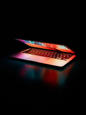Mid-opened Macbook Pro glowing in a dark environment