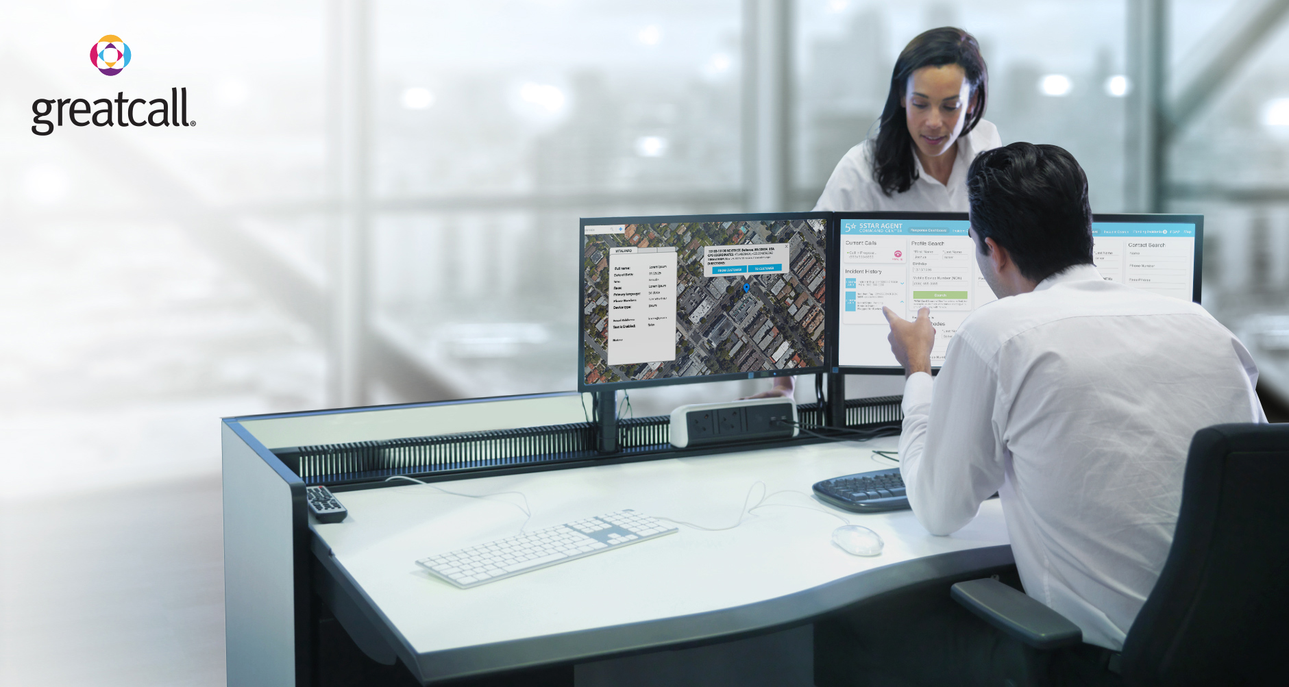 GreatCall stock photo of two people in an office using a computer with three monitors.