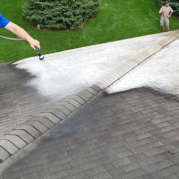 Pressure washing a roof using soft washing process