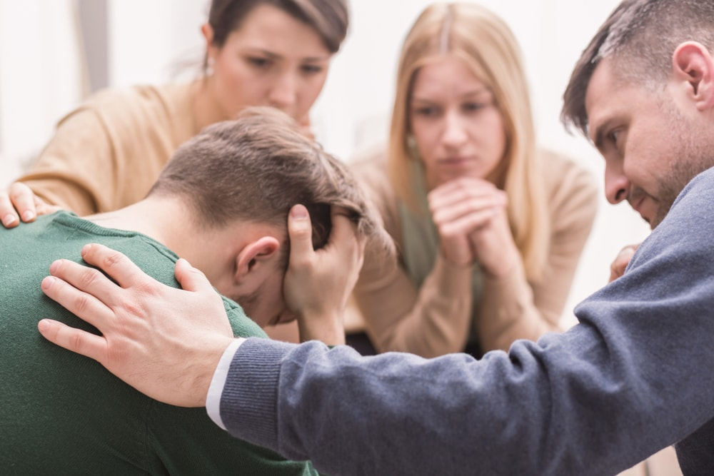 Family consoling a young man