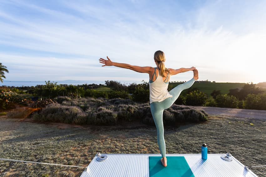 Woman doing yoga on the deck of a luxury travel trailer