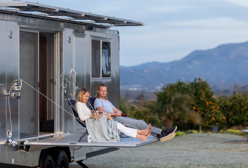 People sitting on the deck of a luxury travel trailer