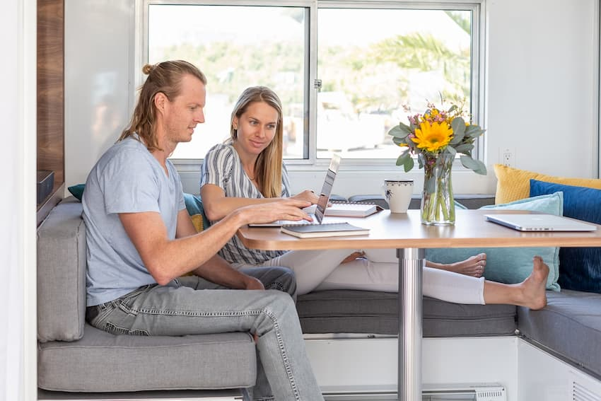 People sitting in the kitchen of a luxury travel trailer