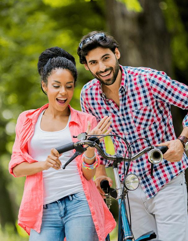 Couple outside walking a bike