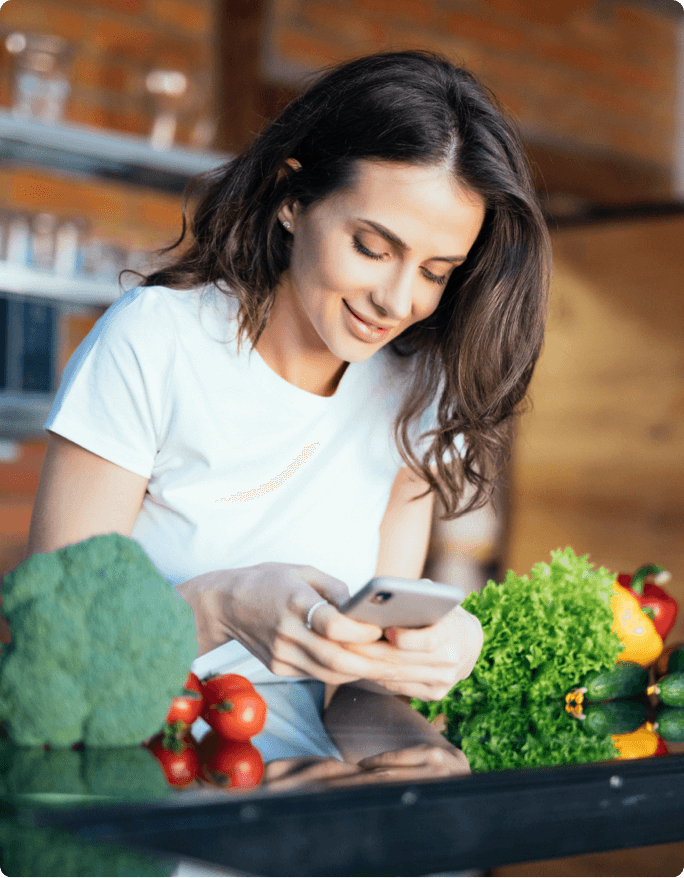 Woman with vegetables on her phone