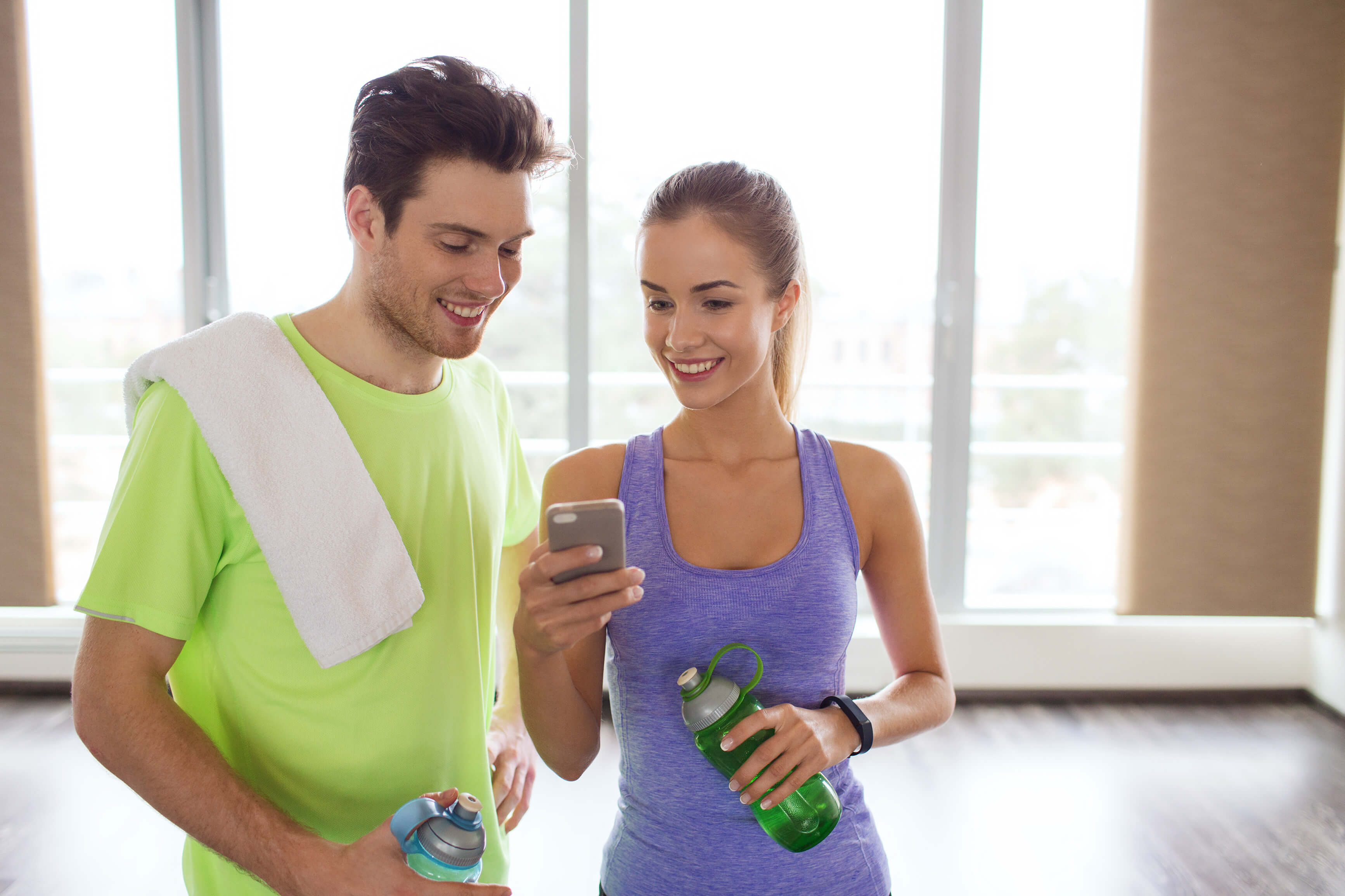 Two people in the gym looking at a phone