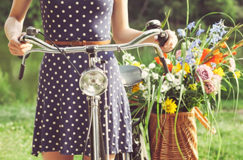 woman in cotton dress with bicyle and flowers