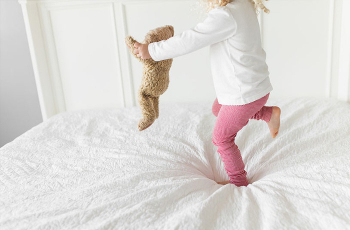 kid jumping on bed