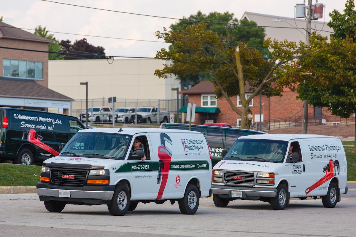 White Vaillancourt Plumbing Trucks driving down Oshawa street