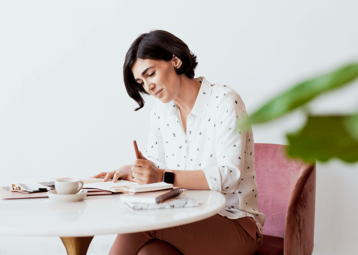 woman writing brand story in notebook
