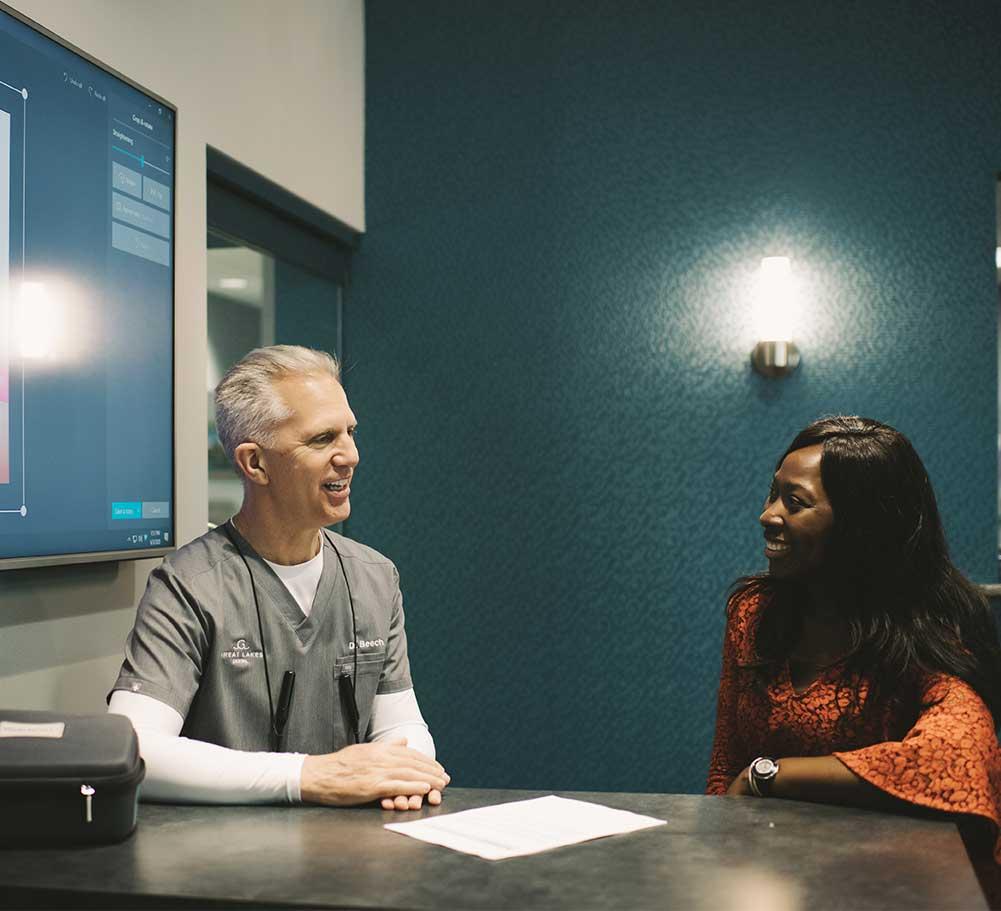 Photo of Dr. Beech explaining sleep apnea laser treatments to a patient