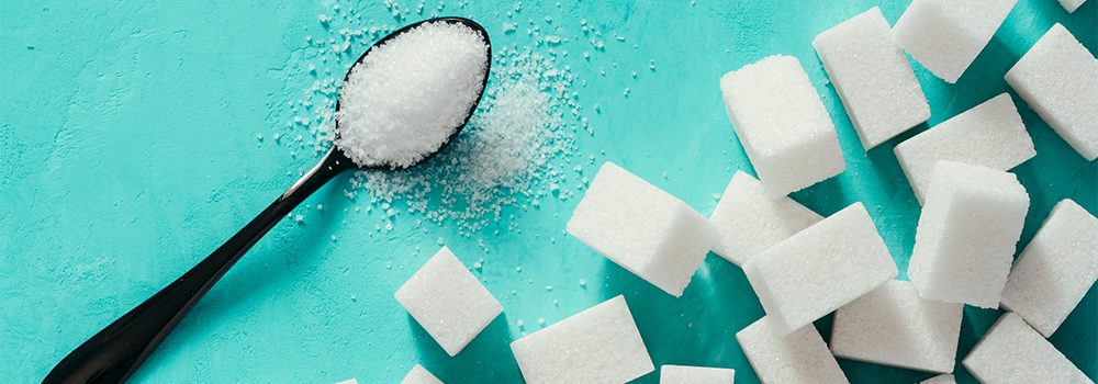 sugar cubes and sugar on a teaspoon blue background