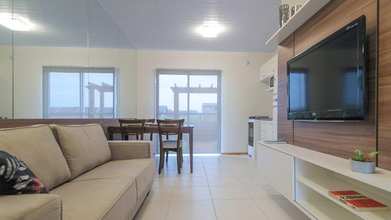 Sala e cozinha decoradas, com saída para o jardim privativo do Residencial Centro Novo em Eldorado do Sul