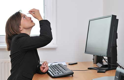 Woman at a desk with dry eye using eye drops. Dr. Shofner treats dry eye disease and chronic dry eye.