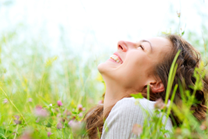 Happy young woman outdoors enjoying a field of flowers without allegies.