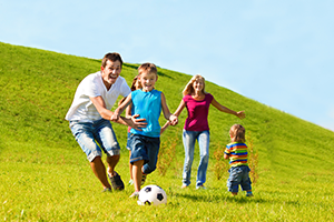 Parents and 3 young children enjoying an outing of kickball - free from sinus infections.