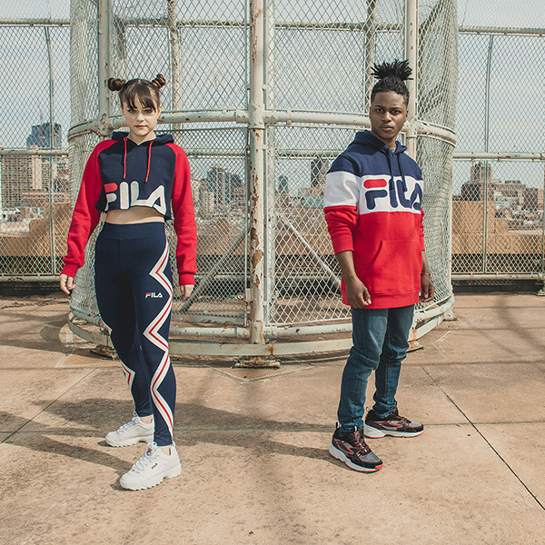 Photo of a young man and woman wearing Fila clothes and shoes.