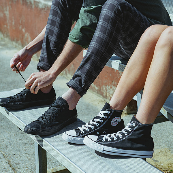 Photo of two teens' legs and feet wearing converse shoes