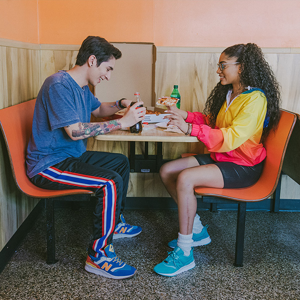 Two young adults in a restaurant booth wearing New Balance Shoes