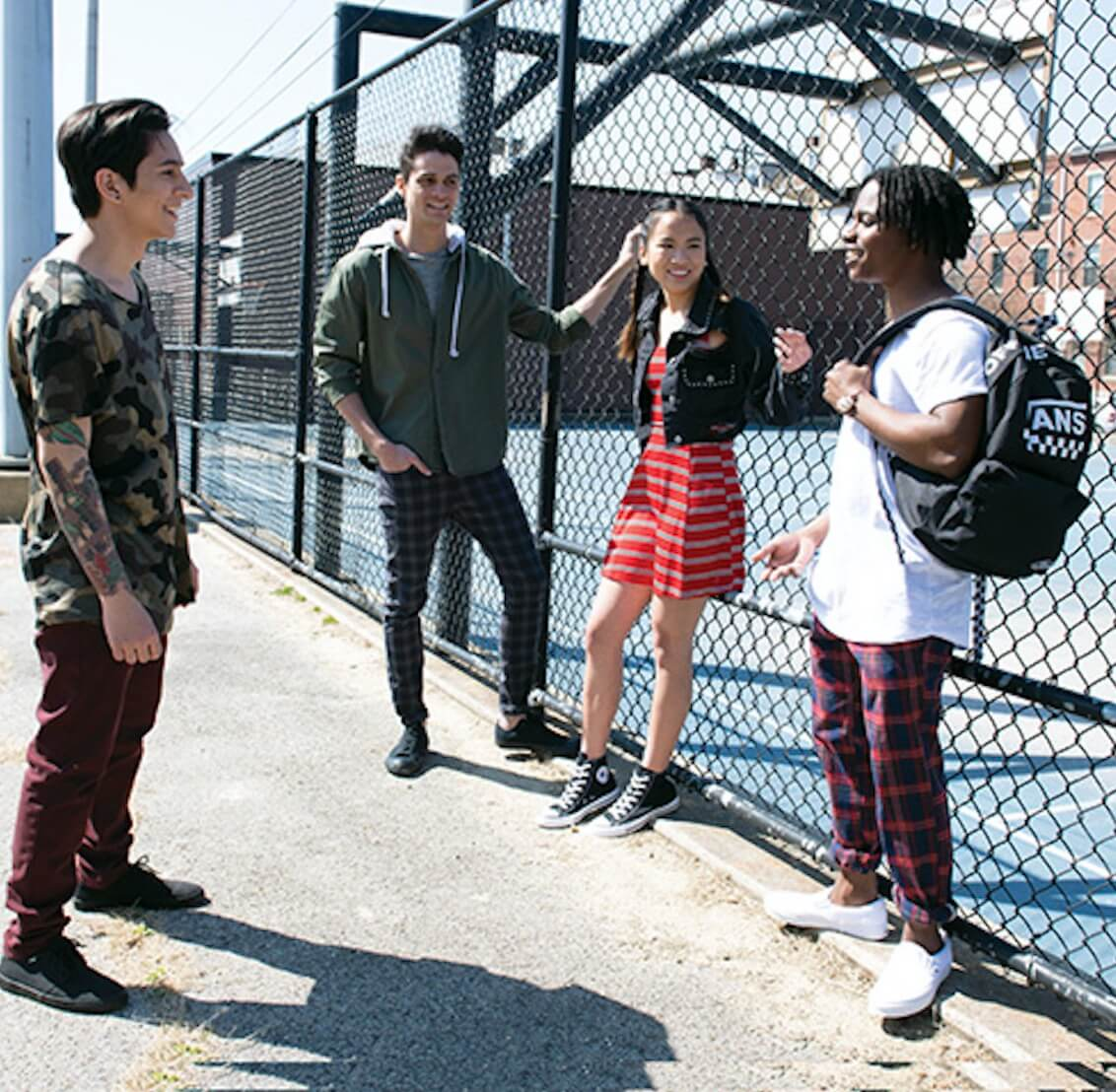 Photo of stylish college students standing next to a fence