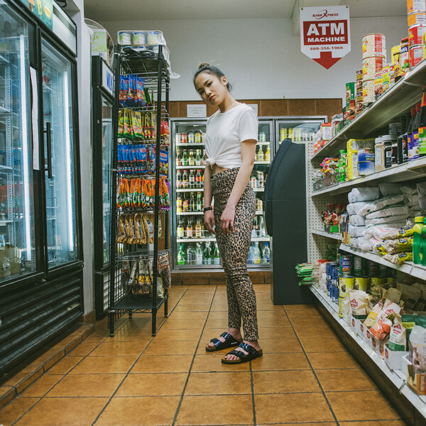 Photo of a young woman in a gas station aisle wearing Birkenstocks