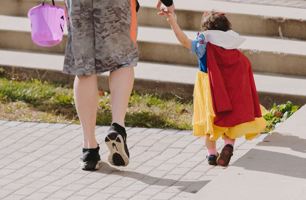 Photo of a young girl dressed as Sleeping beauty holding hands with a parent out of frame