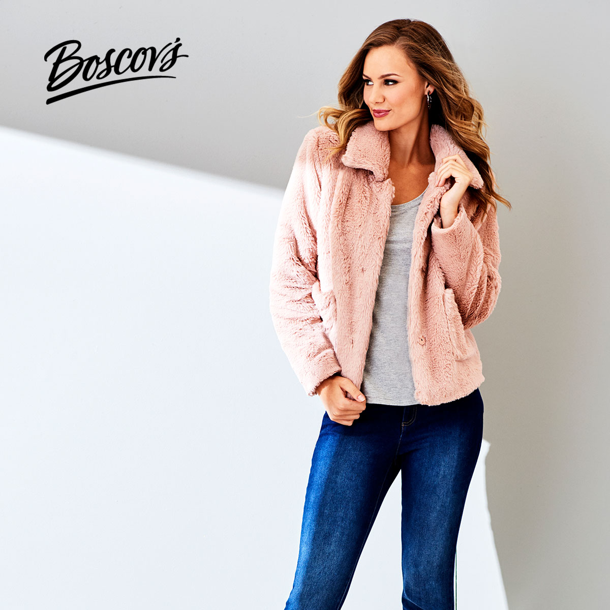 Photo of a young woman wearing a pink fuzzy jacket and jeans