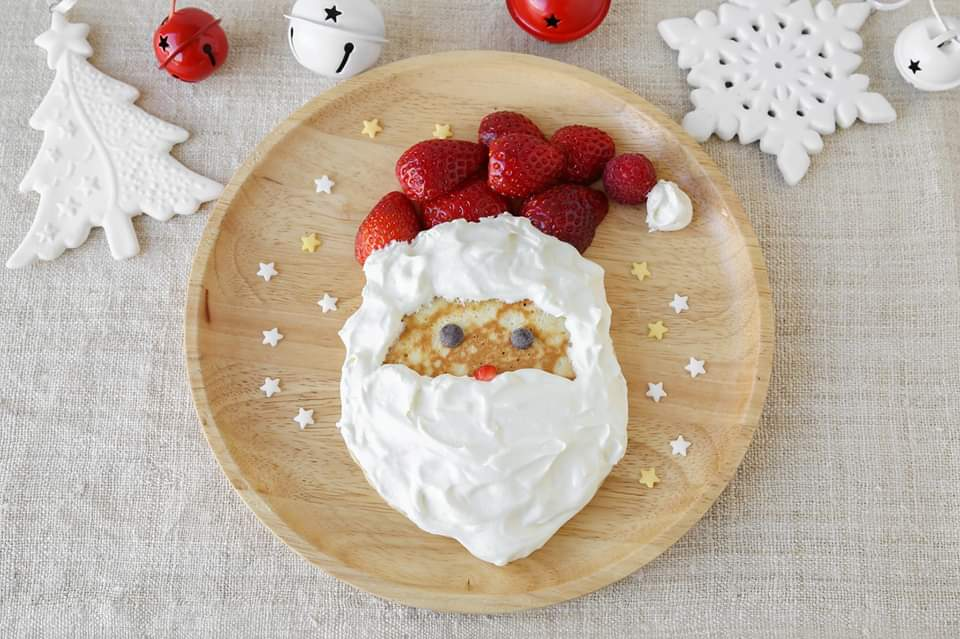 Photo of a pancake with Santa made of strawberries and whip cream on it