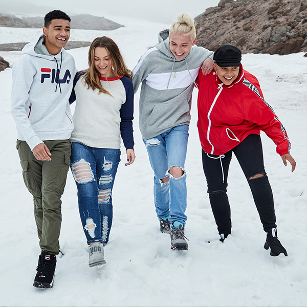 Photo of four teens walking in the snow with new clothes