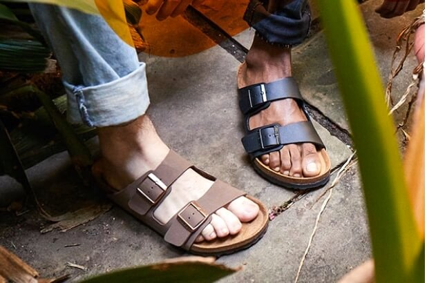 Photo of two people's feet: one wearing black and one wearing brown Birkenstock sandals