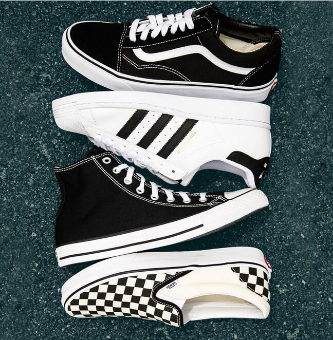 Photo of four different styles of black and white shoes from Vans, Adidas, and Converse
